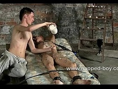 Max Brown is tied gets hot wax poured on him
